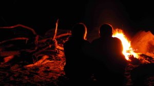 fire on beach while camping in peru